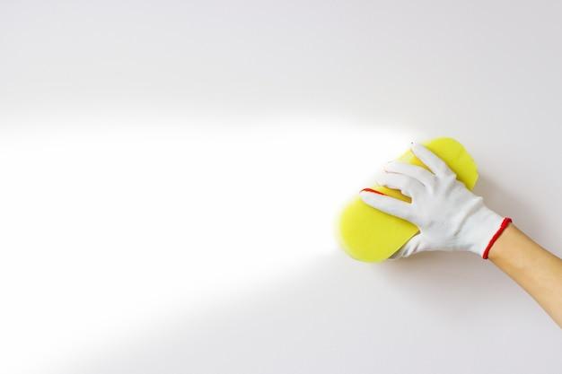 La mano tiene la spugna gialla e lava una parete su uno sfondo bianco con lucentezza pulita. pulizia
