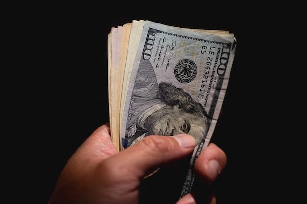 Mano che fora banconote di dollari americani su sfondo nero