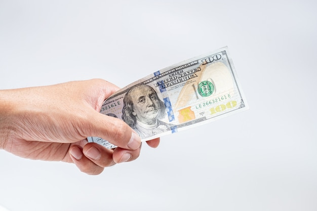 Mano che perfora le banconote dei dollari americani su fondo bianco