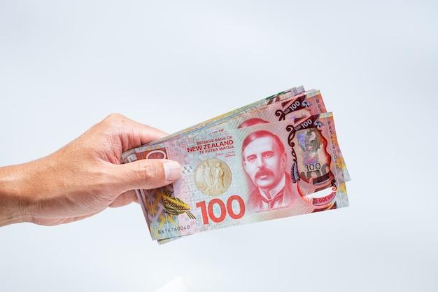 Mano che perfora la nuova zelanda 100 dollari di banconote su sfondo bianco