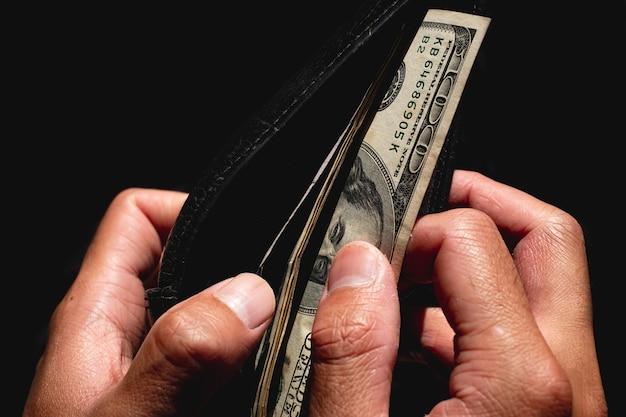 Portafoglio di foratura a mano e banconote in dollari americani su sfondo nero