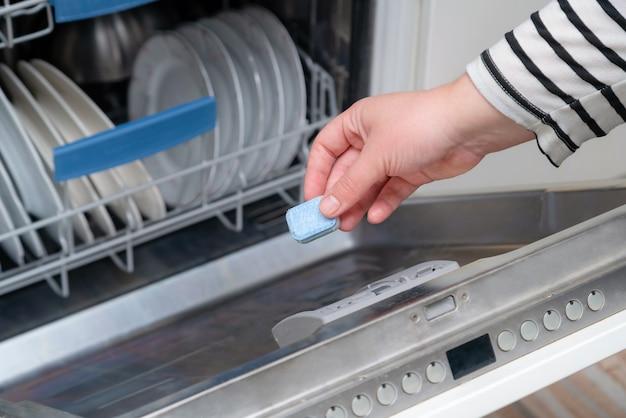 Inserire a mano la capsula di sapone nella lavastoviglie in cucina