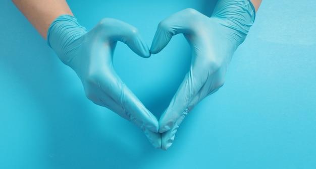 Una mano sta facendo il segno dell'amore con la mano e indossa guanti chirurgici o guanti in lattice su sfondo blu.