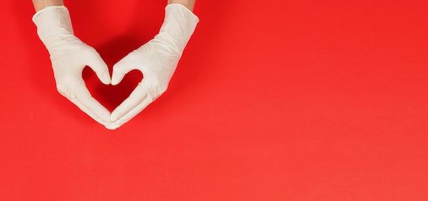 Una mano sta facendo il segno dell'amore con la mano e indossa guanti chirurgici bianchi o guanti in lattice su sfondo rosso.