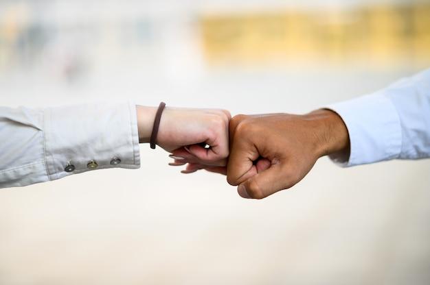 La mano è un pugno che tocca la parte anteriore dell'edificio alto. forza di cooperazione e saluto covid