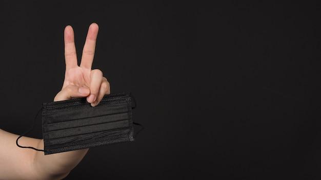 La mano tiene la maschera medica nera e fa il segno della mano di vittoria o pace su sfondo nero.isolato, copia spazio.