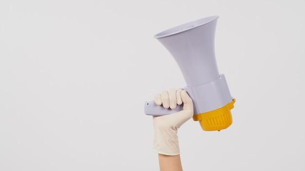 La mano è tenere il megafono e indossare guanti medici su sfondo bianco.