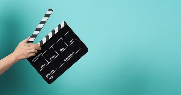 La mano tiene il ciak nero o l'ardesia del film su sfondo verde o menta o tiffany blue.