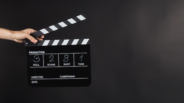 La mano tiene il ciak nero o l'ardesia del film con il numero di scrittura. utilizza nella produzione di video, film, industria cinematografica su sfondo nero.