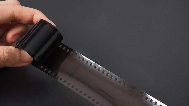 La mano tiene il rotolo di pellicola su sfondo nero.