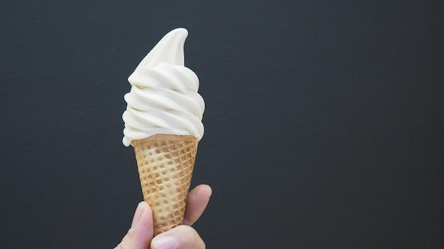 La mano tiene un cono gelato con servizio morbido con fondo nero. Foto Premium