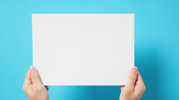 La mano tiene il foglio a4 bianco su sfondo blu.