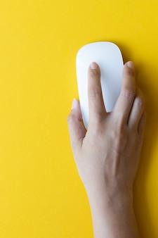 Una mano è sul moderno mouse touch wireless in vetro su sfondo giallo, vista dall'alto