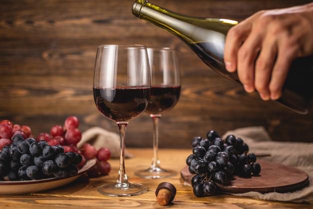 Una mano sta versando il vino rosso secco da una bottiglia in un bicchiere sullo sfondo di un grappolo d'uva su un tavolo di legno