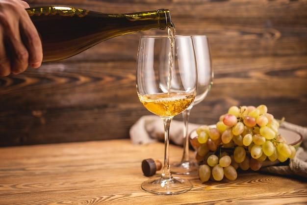 Una mano sta versando il vino bianco secco da una bottiglia in un bicchiere sullo sfondo di un grappolo d'uva su un tavolo di legno