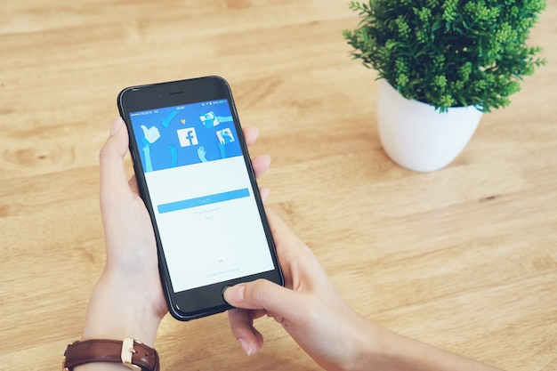 Mano sta premendo lo smartphone dello schermo di facebook