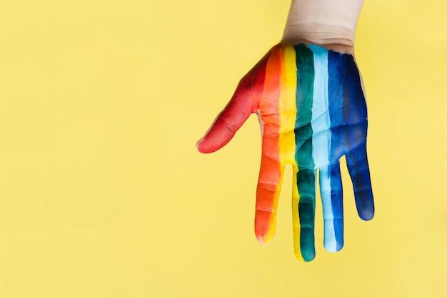 La mano è imbrattata di vernice dell'arcobaleno lgbt. il concetto di amore, tolleranza sessuale, orgoglio lgbt, relazioni omosessuali, omosessualità.