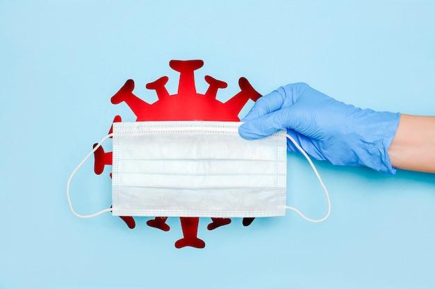 Guanto in lattice a mano e maschera medica attraverso il foro a forma di coronavirus rosso, virus, batteri, microbi su sfondo blu. concetto creativo di protezione contro covid -19 e malattie infettive.