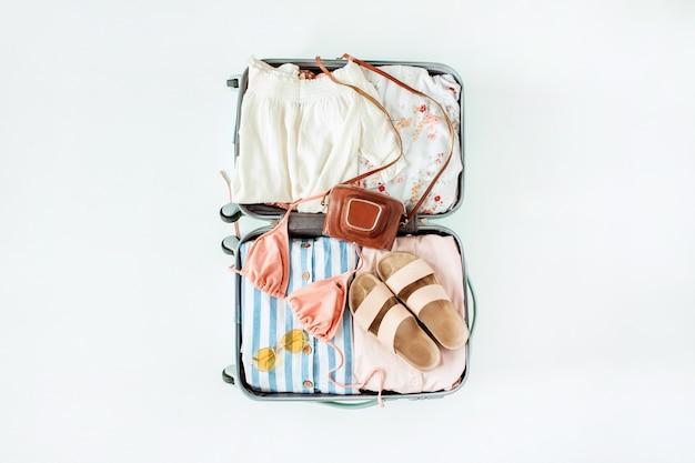 Bagaglio a mano con bikini, occhiali da sole, pantofole, fotocamera retrò e abito su sfondo bianco. composizione di moda per le vacanze di viaggio vista dall'alto.