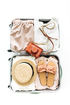 Bagaglio a mano con vestiti da donna alla moda su sfondo bianco. disposizione piatta, vista dall'alto