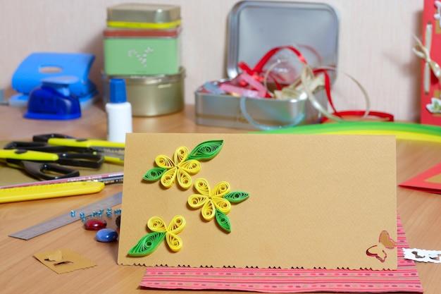 Cartolina di scrapbooking fatta a mano e strumenti sdraiati su un tavolo.