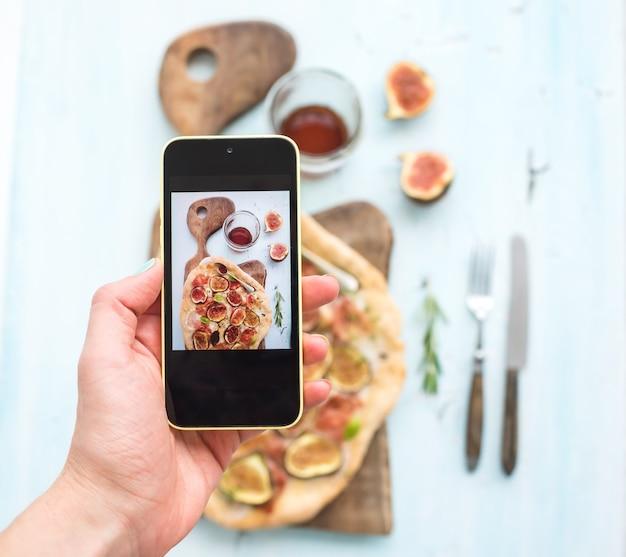 Sparare a mano sul cellulare: rustica pizza fatta in casa con fichi, prosciutto e mozzarella, tavola di legno scuro su sfondo azzurro. vista dall'alto.