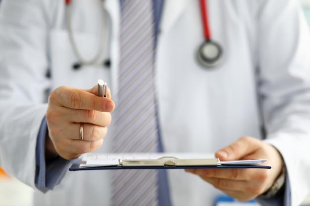 Mano del gp maschio che passa alla penna d'argento paziente che chiede di firmare un primo piano di alcuni documenti cartacei