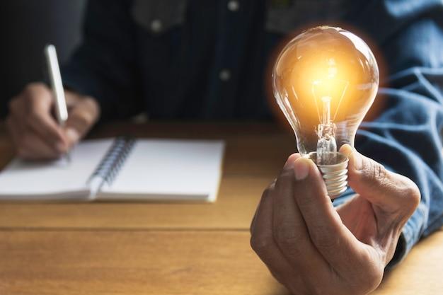 Mano del maschio che tiene una lampadina e copia lo spazio per la contabilità