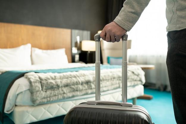 Mano di un viaggiatore maschio o di un uomo d'affari in abbigliamento casual che tiene per la maniglia della sua valigia mentre si trova di fronte al letto finito e va a rilassarsi