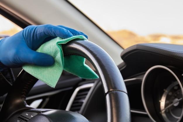 La mano dell'uomo in guanto protettivo blu sta pulendo il volante con un panno.