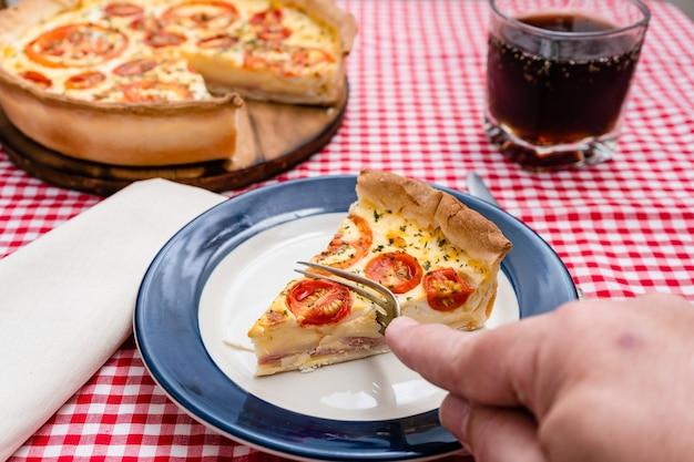 Mano di un uomo che taglia la porzione di prosciutto e torta di formaggio o quiche loraine servita su un piatto. cibo domestico, concetto sano