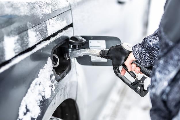Mano di un uomo che riempie il serbatoio del carburante della sua auto durante il congelamento dell'inverno nevoso.