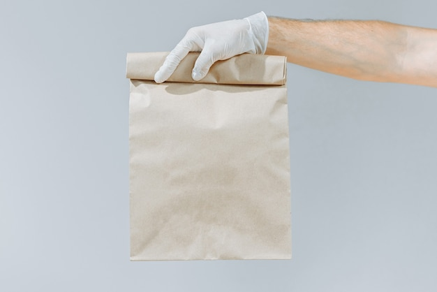 Mano di un uomo in un guanto che tiene una borsa o una borsa marrone per portare fuori