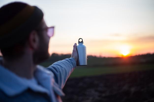 Mano dell'uomo che tiene la bottiglia di alluminio per l'acqua, sullo sfondo del tramonto