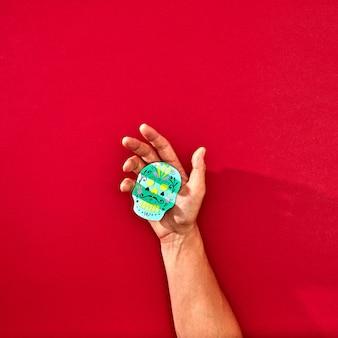 La mano di un uomo tiene un teschio di carta handcraf calaveras attributi della vacanza messicana calaca su uno sfondo rosso con spazio per il testo e la riflessione delle ombre. halloween. lay piatto