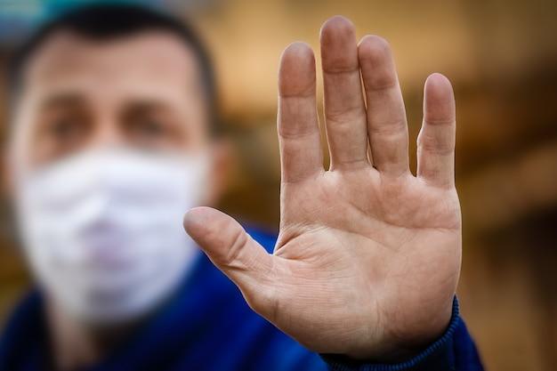 Una mano di un uomo con una maschera di piedi da un coronavirus e aria. protezione dall'aria pm 2.5 inquinata dal virus in europa e asia