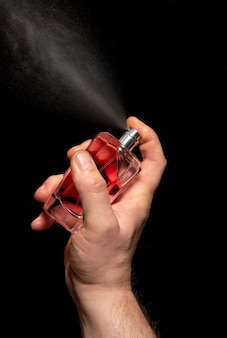 Mano uomo spruzzare profumo su sfondo nero