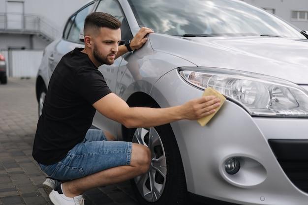 La mano dell'uomo pulisce il faro della sua auto usando l'autolavaggio self-service per tappeti all'aperto