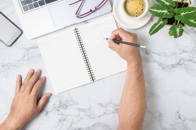 Mano che scrive sul taccuino in bianco con il computer portatile e il caffè sul fondo della tavola in marmo, concetto di affari