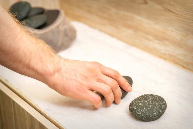 Mano del massaggiatore prendendo massaggio pietre dal tavolo prima delle procedure di massaggio