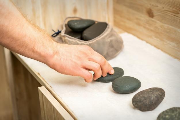 La mano del massaggiatore prende le pietre nere calde da massaggio dal tavolo nella spa