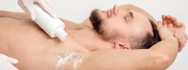 Mano del maestro depilazione versando talco in polvere sull'ascella del giovane prima della procedura di depilazione.