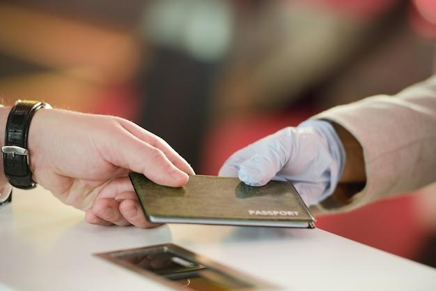 Mano di un uomo maturo che riprende il passaporto dopo la registrazione prima del volo al banco del check in un aeroporto contemporaneo
