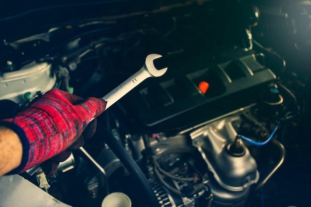 La mano dell'uomo professionale del meccanico tiene gli strumenti di una chiave con il motore di automobile