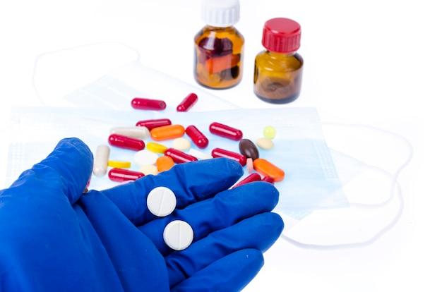La mano nel guanto medico contiene pillole, pillole e capsule colorate