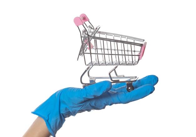 La mano nel guanto medico tiene il carrello della spesa isolato su bianco