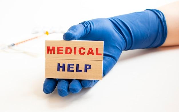 Una mano in un guanto medico tiene cubi di legno con la scritta aiuto medico
