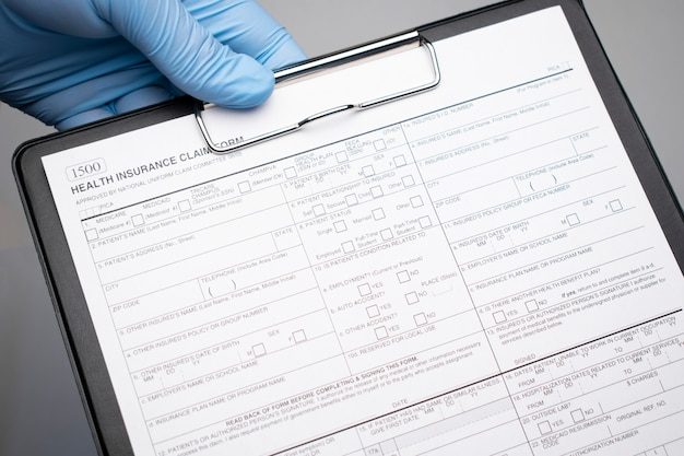 Una mano in un guanto medico indica un testo del primo piano assicurazione sanitaria scritto su un documento.