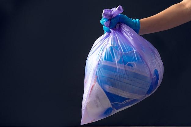 Mano nel guanto medico gettando il sacco della spazzatura