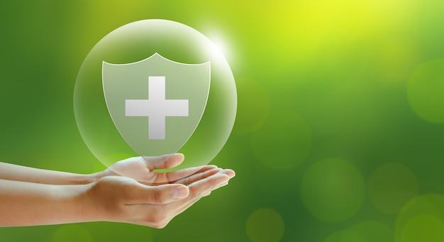 Scudo medico offerta a mano su sfondo verde assicurazione sulla vita familiare assicurazione per cure mediche